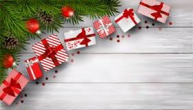 Fondo di Natale con i rami dell'abete ed il mazzo di contenitori di regalo rossi sulla tavola di legno bianca Fotografia Stock