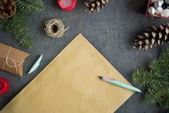 Fondo di Natale con i regali di Natale, la decorazione, la cartolina e la lettera vuota di Natale a Santa sulla parete grigia Immagini Stock