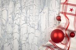 Fondo di Natale con i tovaglioli, le bagattelle rosse ed il nastro su Rus Fotografia Stock