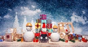 Fondo di Natale con il Babbo Natale, il pupazzo di neve ed i giocattoli con i presente Fotografia Stock