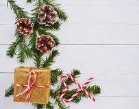 Fondo di Natale con il bastoncino di zucchero, il regalo, i coni ed i rami dell'abete sopra la tavola di legno bianca fotografie stock libere da diritti