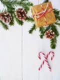 Fondo di Natale con il bastoncino di zucchero, il regalo, i coni ed i rami dell'abete sopra la tavola di legno bianca fotografia stock
