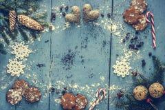 Fondo di Natale con il fiocco di neve, il pan di zenzero, il bastoncino di zucchero, i cuori e la decorazione dell'albero di abet Immagini Stock