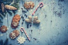Fondo di Natale con il pan di zenzero, il bastoncino di zucchero, i cuori e l'albero di abete Fotografie Stock Libere da Diritti