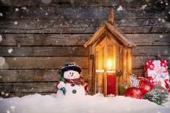 Fondo di Natale con il pupazzo di neve e la lanterna Fotografia Stock Libera da Diritti
