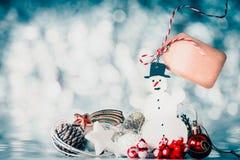 Fondo di Natale con il pupazzo di neve, la decorazione festiva e l'etichetta in bianco con il posto per testo al fondo del bokeh  Immagine Stock