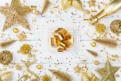 Fondo di Natale con il regalo dorato o scatola, champagne e decorazioni attuali di festa sulla vista bianca del piano d'appoggio  fotografie stock libere da diritti