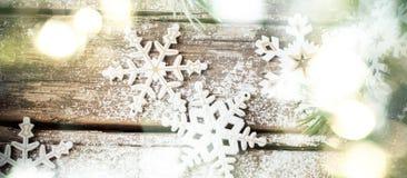 Fondo di Natale con incandescenza luminosa ed i fiocchi di neve decorativi di legno bianchi Fotografie Stock