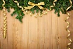 Fondo di Natale con l'abete, l'arco ed i nastri su legno Fotografia Stock Libera da Diritti
