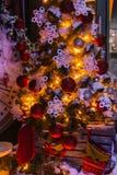 Fondo di Natale con l'albero di abete illuminato e camino, orologio alla casa fotografie stock libere da diritti