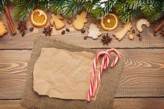 Fondo di Natale con l'albero di abete della neve, spezie, coo del pan di zenzero Immagini Stock