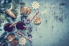 Fondo di Natale con la decorazione dell'albero del vin brulé, del pan di zenzero, del bastoncino di zucchero e di abete Immagine Stock