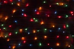 Fondo di Natale con la plancia di legno di marrone delle luci Fotografia Stock Libera da Diritti