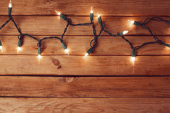 Fondo di Natale con la tavola e le luci di Natale di legno vuote Immagini Stock