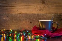 Fondo di Natale con la tazza avvolta in sciarpa e nelle luci rosse sopra Fotografia Stock