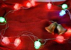 Fondo di Natale con le campane su una sciarpa rossa immagini stock