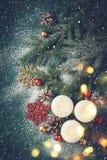 Fondo di Natale con le candele brucianti e la neve Fotografia Stock