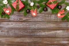 Fondo di Natale con le decorazioni ed i contenitori di regalo sul bordo di legno Fotografia Stock