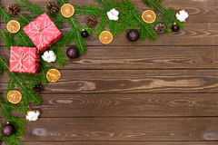 Fondo di Natale con le decorazioni ed i contenitori di regalo sul bordo di legno Immagini Stock