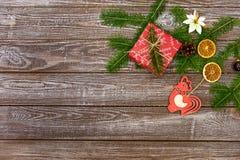 Fondo di Natale con le decorazioni ed i contenitori di regalo sul bordo di legno Immagine Stock