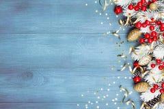 Fondo di Natale con le decorazioni nevose dell'albero e di festa di abete sulla vista di legno blu del piano d'appoggio Cartolina immagini stock