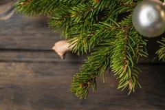 Fondo di Natale con le decorazioni sul bordo di legno Il ramo del pino del nuovo anno denuclea Immagine Stock