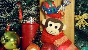 Fondo di Natale con le luci e la scimmia della candela sul calzino rosso stock footage