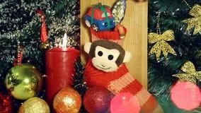 Fondo di Natale con le luci ed i regali della candela sul calzino rosso con la scimmia video d archivio