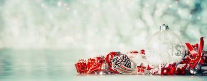 Fondo di Natale con le palle di vetro e decorazione festiva rossa al fondo del bokeh di inverno, vista frontale Immagini Stock