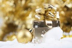 Fondo di Natale con neve, la palla di Natale ed il contenitore di regalo Immagini Stock