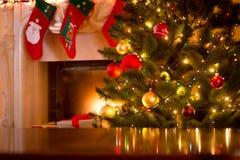 Fondo di Natale della tavola contro l'albero di Natale e il firepla fotografia stock libera da diritti