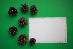 Fondo di Natale delle pigne con la carta di Libro Bianco Concetto di Buon Natale e del nuovo anno immagini stock libere da diritti
