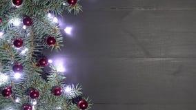 Fondo di natale di legno nero decorato con i rami dell'abete Pino decorato con le bagattelle e le luci brillanti stock footage