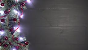 Fondo di natale di legno nero decorato con i rami dell'abete Pino ornato con i coriandoli rossi delle bagattelle e le luci luccic stock footage