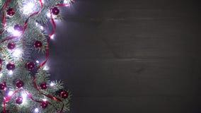 Fondo di natale di legno nero decorato con i rami dell'abete Pino ornato con i coriandoli rossi delle bagattelle e le luci luccic video d archivio