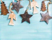 Fondo di Natale o del nuovo anno: gli angeli di legno, le stelle ed i piccoli abeti sopra il blu hanno dipinto il contesto, spazi Fotografia Stock