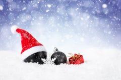 Fondo di Natale - palle nere decorate su neve con i fiocchi di neve e le stelle Fotografia Stock