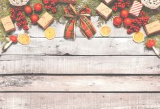 Fondo di Natale - palle rosse, regali, bacche rosse, arancia, funghi decorativi, palle tricottate, arco del tartan, mini regali - Fotografia Stock