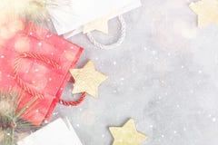 Fondo di Natale: sacchetti della spesa, contenitori di regalo e stelle d'oro sotto neve Fotografie Stock Libere da Diritti
