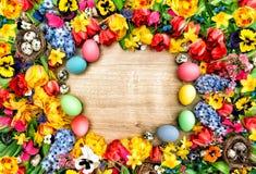 Fondo di Pasqua con i fiori della molla e le uova colorate Immagine Stock