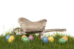 Fondo di Pasqua con le uova colorate nell'erba ed in una carriola di legno Immagine Stock