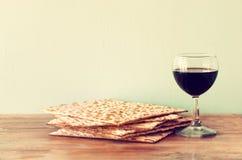 Fondo di pesach. vino e matzoh (pane ebreo di pesach) sopra fondo di legno. Immagini Stock