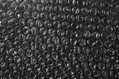 Fondo di plastica di struttura dell'involucro di bolla sul nero Fotografie Stock