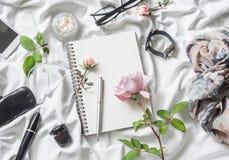Fondo di prodotti piano di bellezza di disposizione Il blocco note, è aumentato, profuma, mascara, orologi, vetri, cuffie, telefo Fotografie Stock