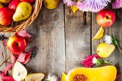 Fondo di ringraziamento o del raccolto con la struttura dei frutti, dei fiori, della zucca e delle foglie autunnali su una tavola Immagini Stock Libere da Diritti