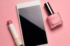 Fondo di rosa pastello dello smalto, del rossetto e del telefono cellulare Immagini Stock