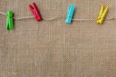 Fondo di struttura della tela di sacco con le clip di legno variopinte Immagine Stock Libera da Diritti