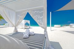 Fondo di stupore di vacanze estive Paesaggio di lusso della spiaggia con il baldacchino e le chaise-lounge bianchi della spiaggia fotografia stock libera da diritti