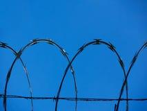 Fondo di un recinto del barbwire contro un cielo blu che forma un modello geometrico dei archs orizzontali immagine stock