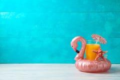 Fondo di vacanze estive con il galleggiante dello stagno del fenicottero e del succo d'arancia sulla tavola di legno fotografia stock